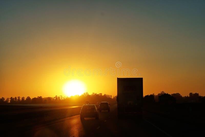 Fahren in einen Sonnenuntergang hinunter die Autobahn lizenzfreies stockbild