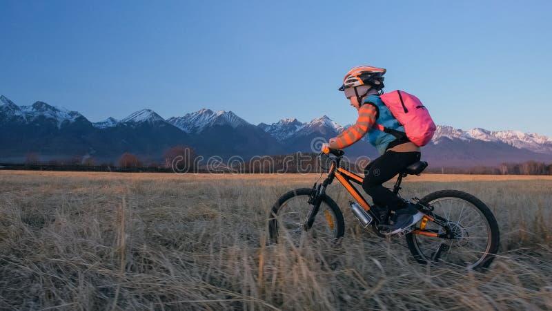 Fahren kaukasische Fahrten der Kind eins auf dem Weizengebiet rad Orange Zyklus des Schwarzen des kleinen Mädchens Reitauf Hinter stockbilder