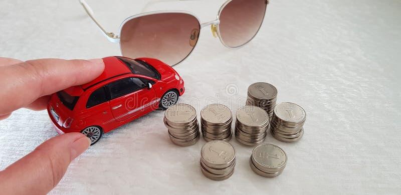 Fahren kleinen roten abarth Fiats 500 Spielzeugs auf weißer Tabelle nahe Sonnenbrille und Stapel von israelischen Schekelmünzen lizenzfreies stockfoto