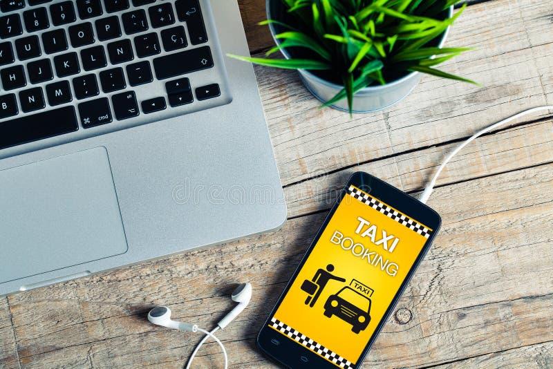 Fahren Sie Buchungsapp auf einem intelligenten Telefonschirm mit einem Taxi lizenzfreie stockbilder