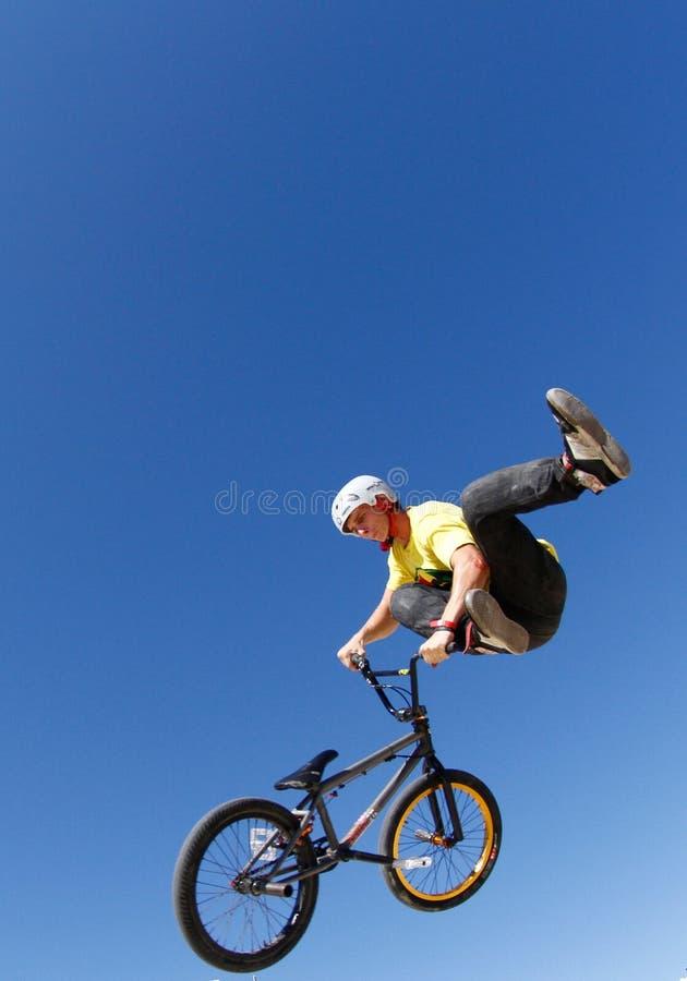 Fahren Sie den betrügenden Reiter beim Springen während der Fahrradwettbewerbsvertikale rad lizenzfreie stockfotografie