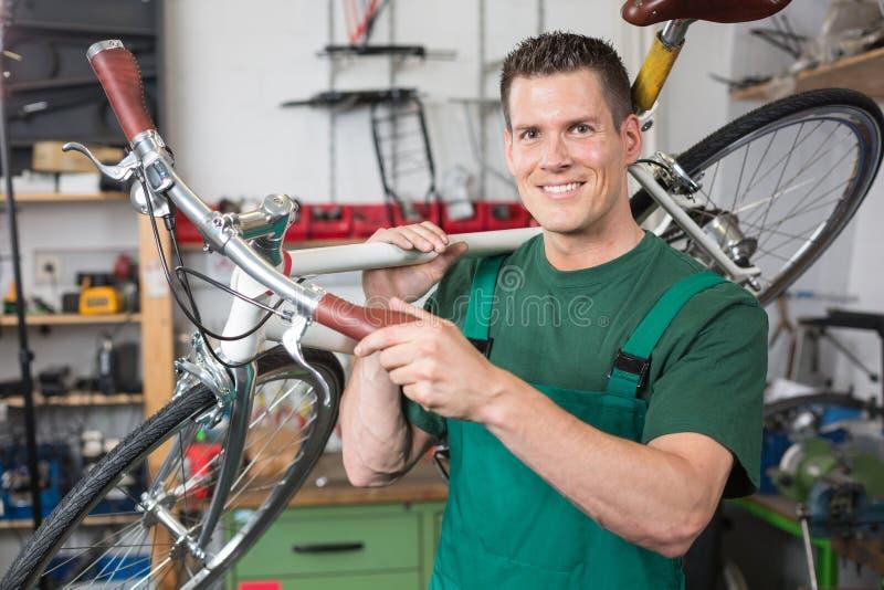 Fahren Sie den Mechaniker rad, der ein Fahrrad beim Werkstattlächeln trägt lizenzfreie stockfotografie