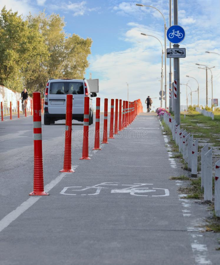 Fahren Sie Weg im Park rad, der mit roten Straßenspalten eingezäunt wird stockfotografie