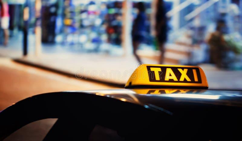 Fahren Sie Zeichen auf dem Dach eines Autos mit einem Taxi stockfotos