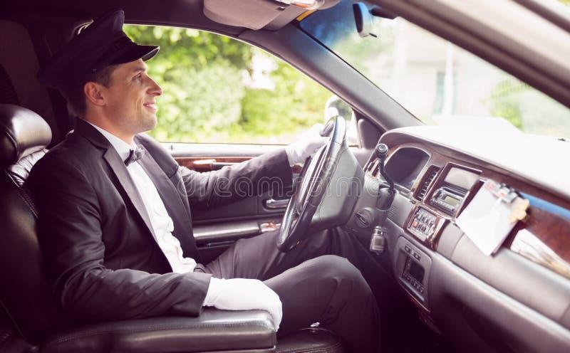 Fahrender und lächelnder Limousinenfahrer stockfotografie