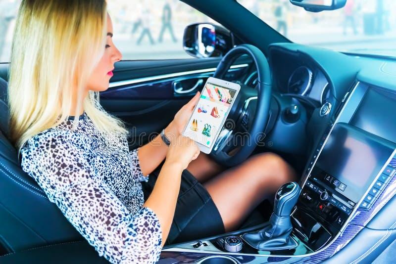 Fahrer der jungen Frau, der einen Tablet-Computer im Auto verwendet stockbild