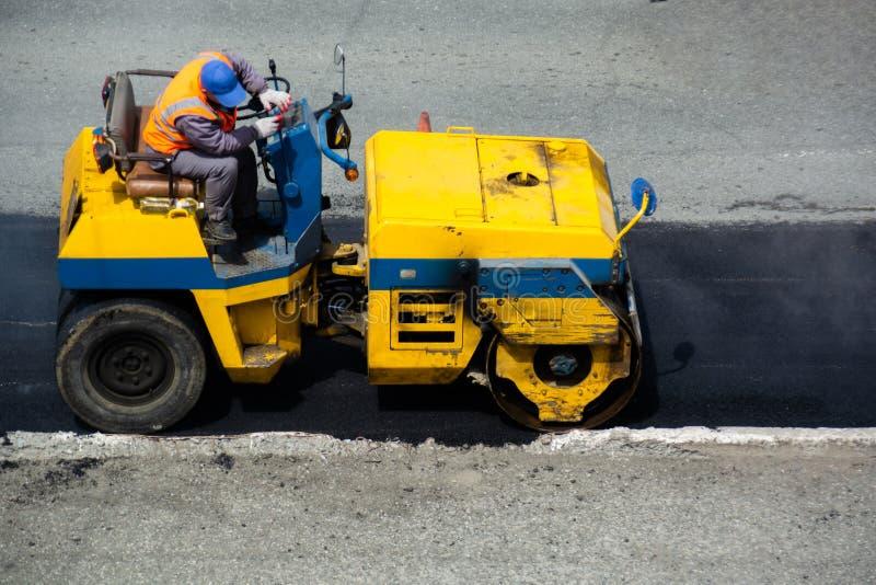Fahrer des Bodenverdichters neue Schicht Asphalt planierend stockbild