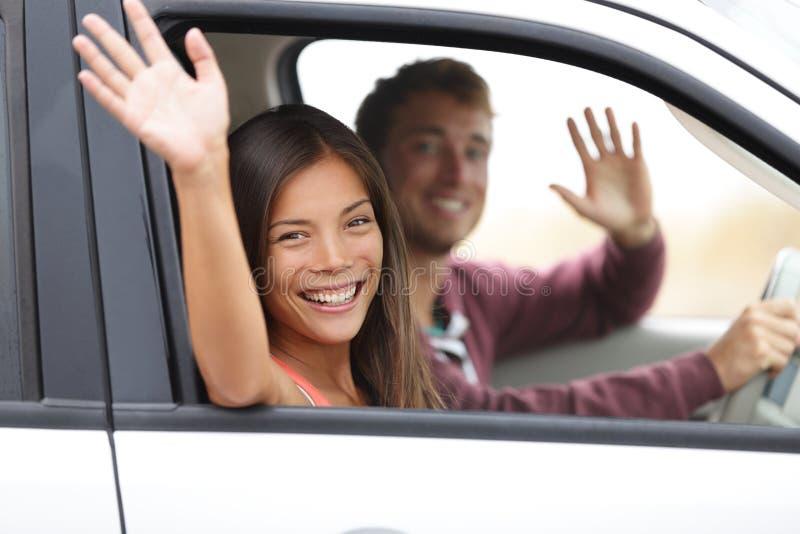 Fahrer, die beim Autowellenartig bewegen glücklich an der Kamera fahren stockbilder
