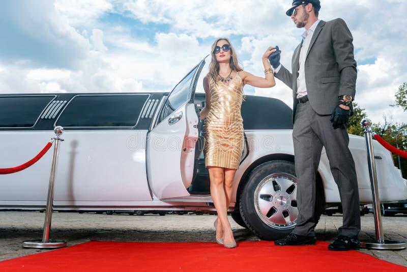Fahrer helfende Promi-Frau oder Stern aus Limousine auf rotem Teppich heraus stockfotografie