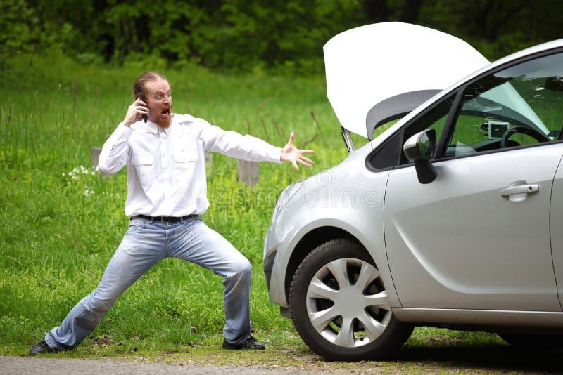 Fahrer wütend mit Handy ein defektes Auto stockfotografie