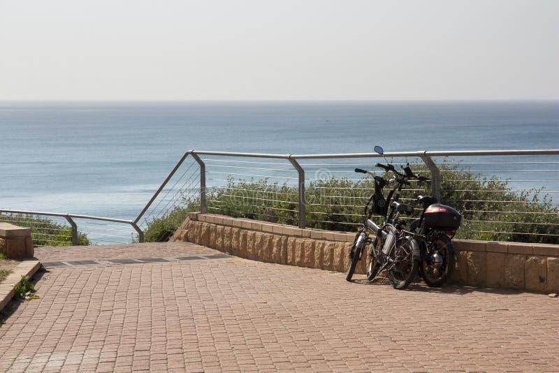 Fahrräder werden auf der Ufergegend am Abfall zum Meer geparkt lizenzfreies stockbild
