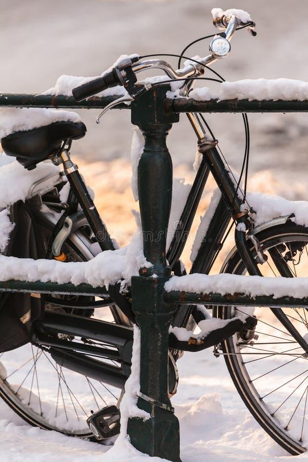 Fahrrad abgedeckt mit Schnee auf einer Kanalbrücke lizenzfreie stockbilder