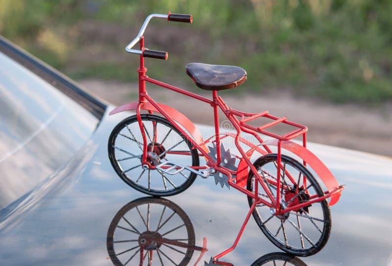 Fahrrad auf der Oberfläche der Haube eines Autos mit Reflexion stockfotos