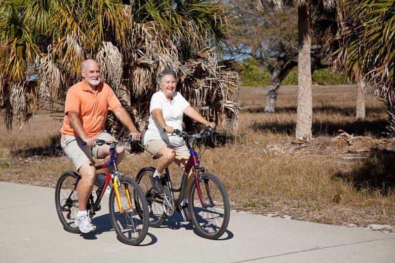 Fahrrad, das ältere Paare reitet stockbilder