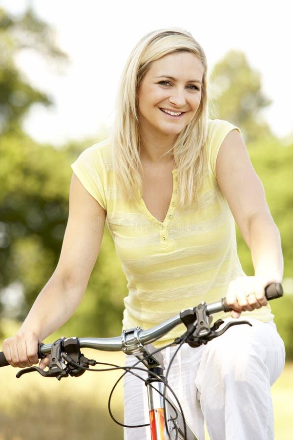 Fahrrad der jungen Frau Reitin der Landschaft stockfotografie