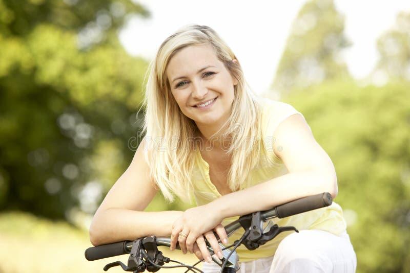 Fahrrad der jungen Frau Reitin der Landschaft lizenzfreies stockbild