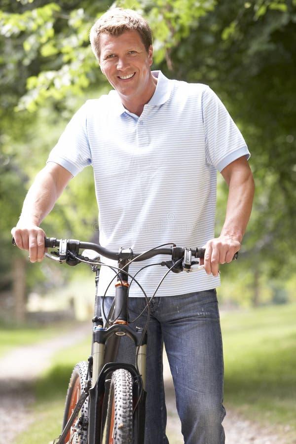 Fahrrad des jungen Mannes Reitin der Landschaft lizenzfreies stockbild
