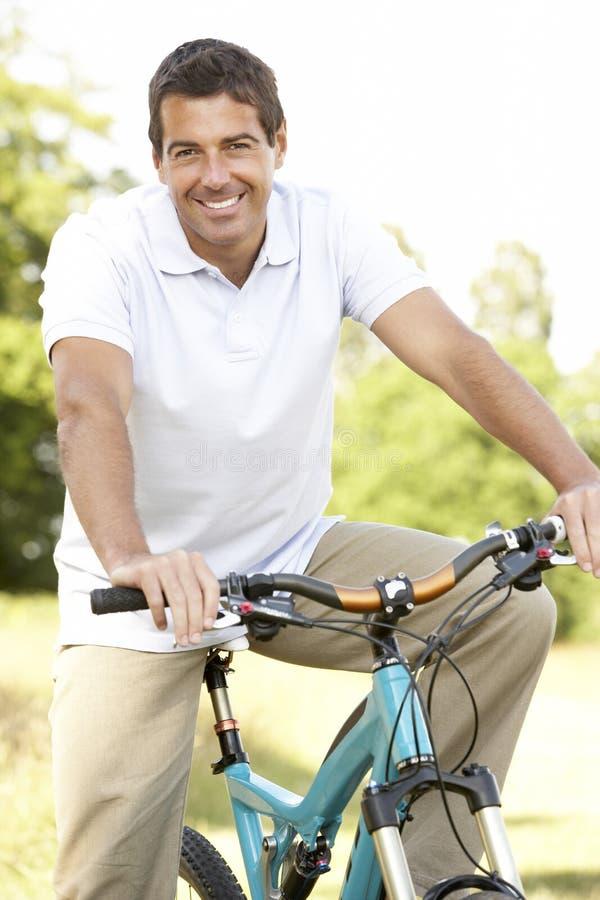 Fahrrad des jungen Mannes Reitin der Landschaft lizenzfreie stockfotos