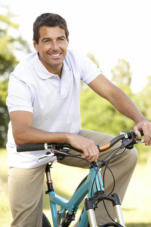 Fahrrad des jungen Mannes Reitin der Landschaft stockbild