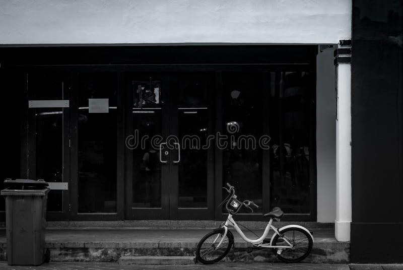 Fahrrad für Miete geparkt auf konkretem Boden vor Bürogebäude Fahrrad für Stadtrundfahrt Verlassenes Fahrrad geparkt nahe Papierk lizenzfreies stockbild