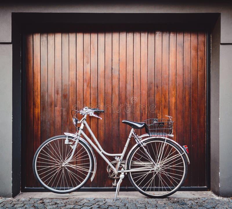 Fahrrad geparkt vor einem Garagentor lizenzfreies stockbild