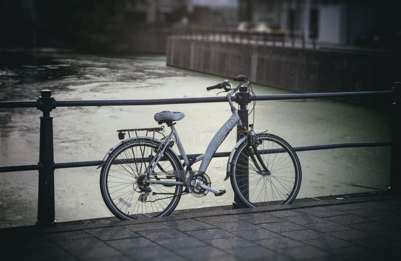 Fahrrad parkte auf Brücke über Stadtfluß, undeutlicher Hintergrund stockfoto