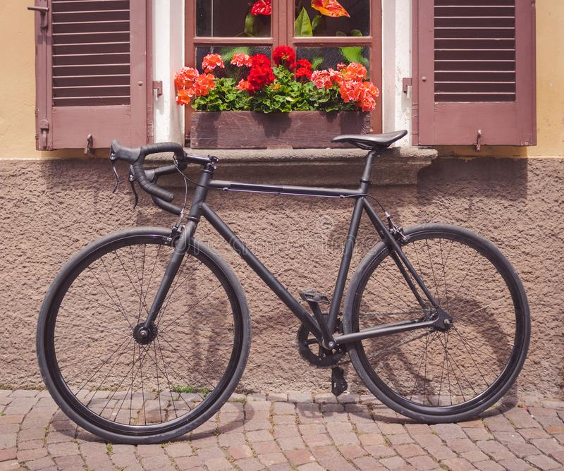 Fahrrad voll gesetzt unter ein Fenster von Blumen stockfotografie