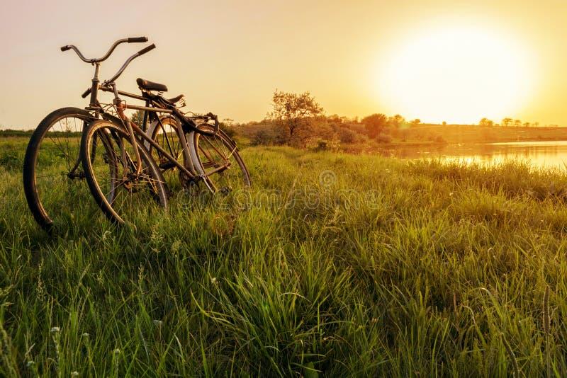 Fahrrad zwei nahe dem Seesonnenunterganghintergrund Zwei Weinlesefahrräder am Sonnenuntergang Das Konzept von Romance und von Lie stockbild