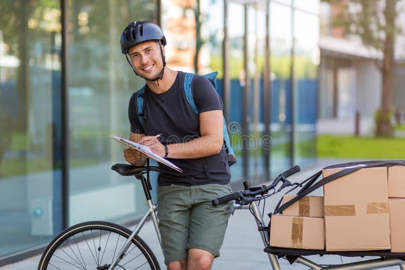 Fahrradkurier, der eine Lieferung macht stockbild