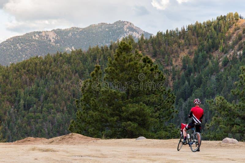 Fahrradreiter und felsiger Bergblick stockfoto