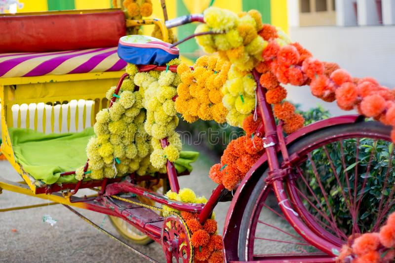 Fahrradrikscha bedeckt mit mehrfarbigen Blumen für eine Hochzeit in Indien stockbilder