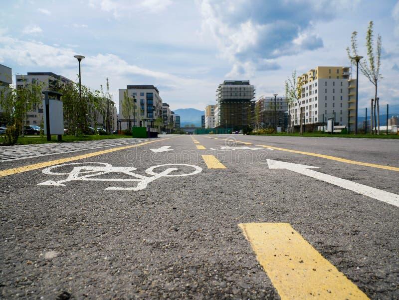 Fahrradstraße auf dem Asphalt, führend zu ein neues modernes residentual Viertel lizenzfreie stockbilder