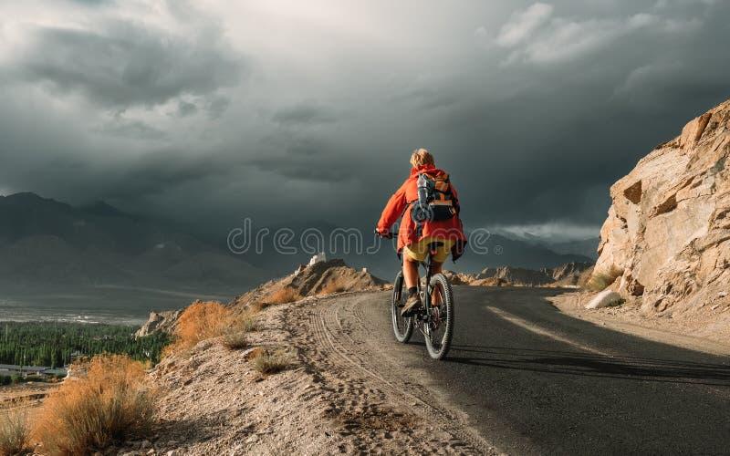 Fahrradtourist f?hrt auf Himalaja-Gebirgsstra?e auf Weise zu buddist Kloster stockfoto