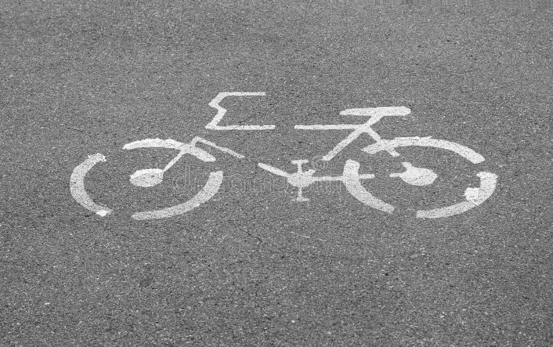 Fahrradzeichen auf konkreter Bahnstraße stockfotografie