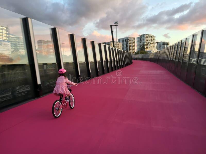 Fahrt des jungen Mädchens ein Fahrrad auf hellem rosa cycleway in Auckland neu stockfotografie