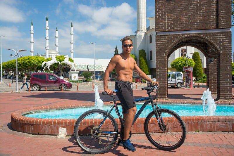Fahrt des jungen Mannes fährt ohne Hemden im Sommer in einem Touristen c rad stockbild