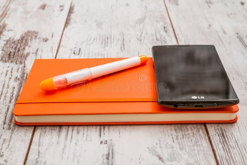 Fahrwerk Smartphone, orange Stift und Notizbuch lizenzfreies stockbild