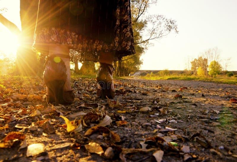 Fahrwerkbeine der Frau, die auf Herbstblätter treten stockfotografie