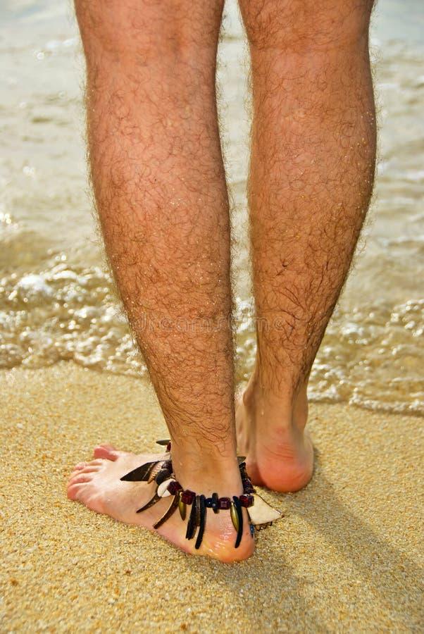 Fahrwerkbeine des Mannes auf Sand durch Meer stockfotos