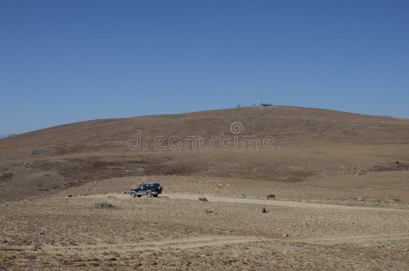 Fahrzeug auf Straße von spärlichen Nationalparkebenen und von Bergen Skardu Pakistan Deosai lizenzfreie stockfotos