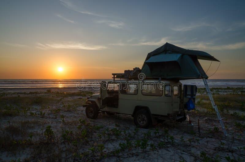 Fahrzeug 4x4 nicht für den Straßenverkehr mit dem Dachspitzenzelt, das auf Strand während des Sonnenuntergangs, Casamance, Senega stockfotografie