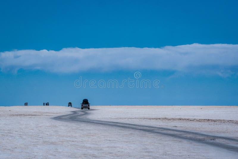 Fahrzeugfahren durch Salar de Uyuni-Salzebenen stockbilder