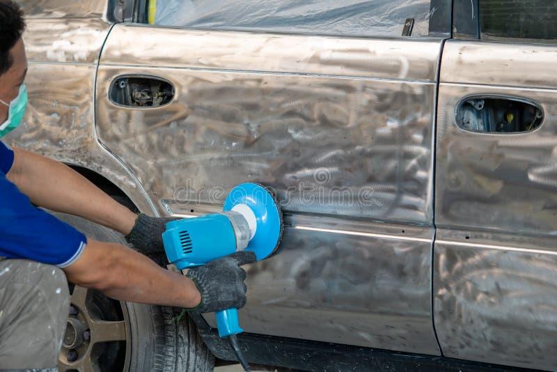 Fahrzeugkarosseriearbeit nach dem Unfall durch das Vorbereiten des Automobils für das Malen während der Reparatur stockfotografie