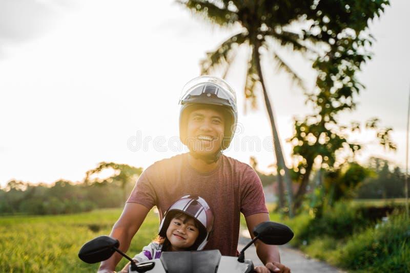 Fahter和他的孩子喜欢乘坐摩托车滑行车 库存图片