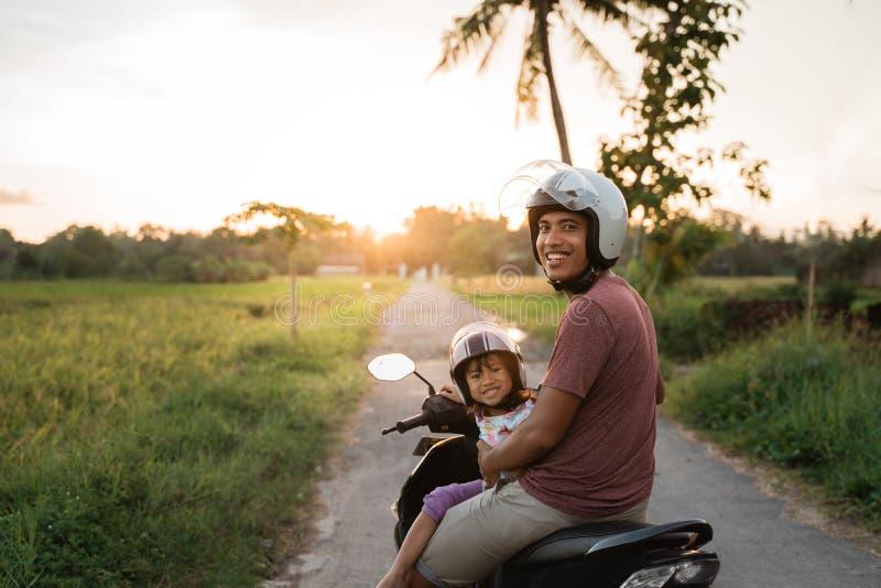 Fahter ed il suo bambino godono di di guidare il motorino del motociclo fotografie stock
