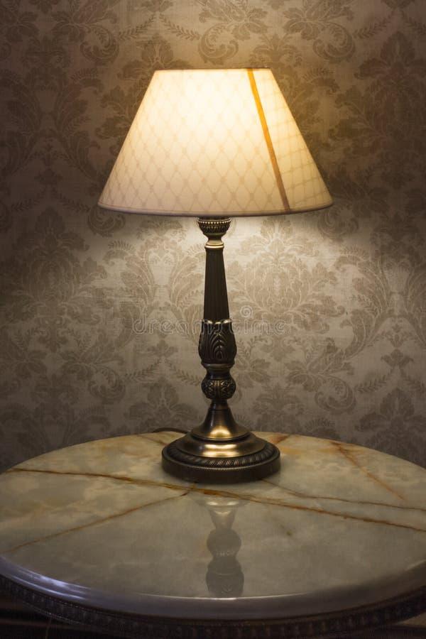 Faibles lumières dans la chambre à coucher d'une lampe de bureau photographie stock libre de droits