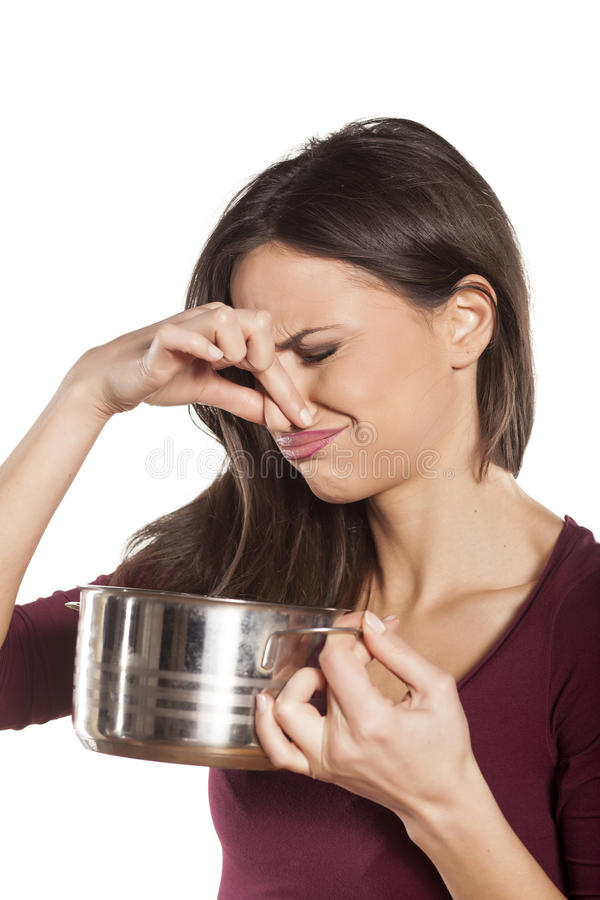 Failed meal. Disgusted woman holding a pot with food and pinching her nose on white background stock photo