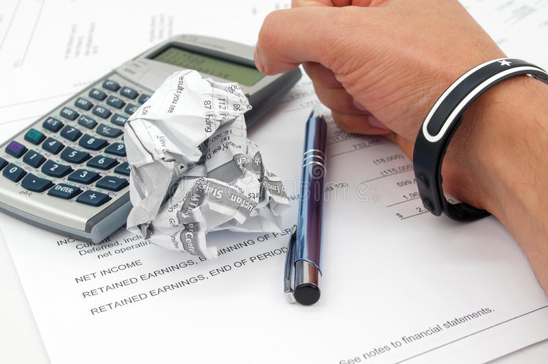 Failing to make right audit. A photo shows a man's hand with calculater and pen and papers trying to make his own audit but it's not working The photo was shut royalty free stock photography