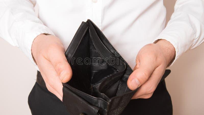 Faillissement - Zakelijke persoon met een lege portefeuille De man die blijk geeft van inconsistentie en gebrek aan geld en niet  royalty-vrije stock foto