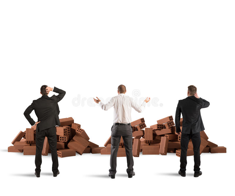 Failure of a building project. Businessmen confused look at a building brick shattered stock images